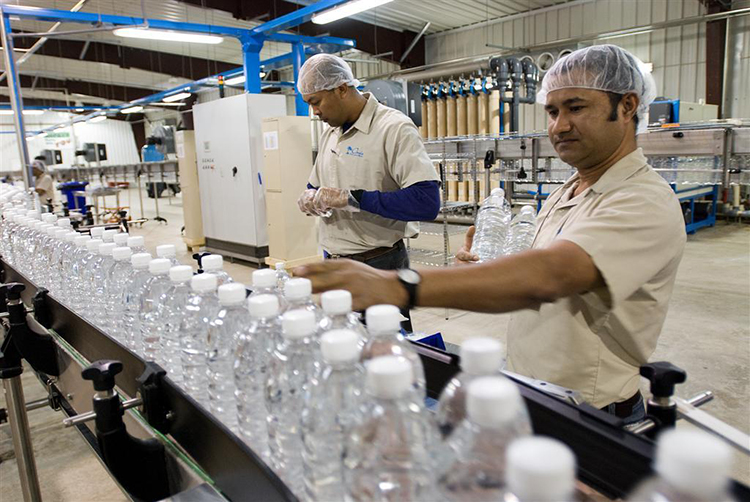 Employees at the Oasis International Waters water purification and bottling plant test for bottle-cap tightness on the production line at Joint Base Balad, Iraq, March 7. The Army saves approximately $900,000 a month using the six water bottling plants in theater.